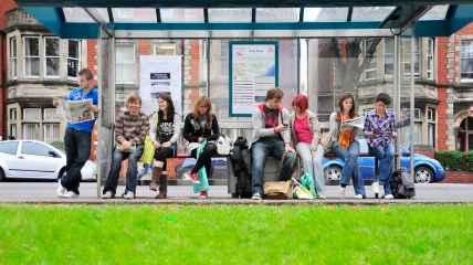 a group of people sitting at a bus stop