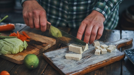 a person cutting tofu on a wooden chopping board