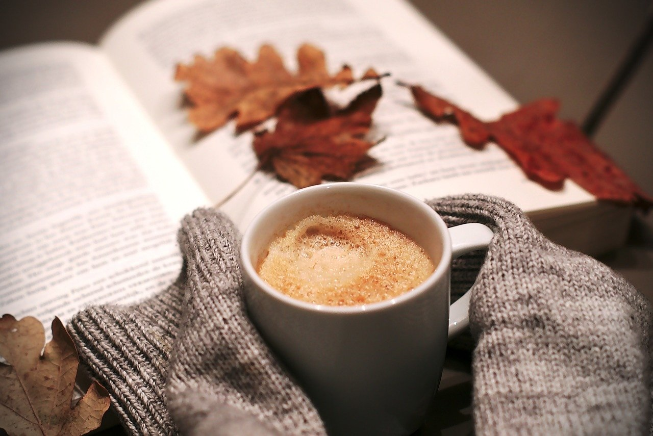 a cup of coffee with an open book with leaves on top