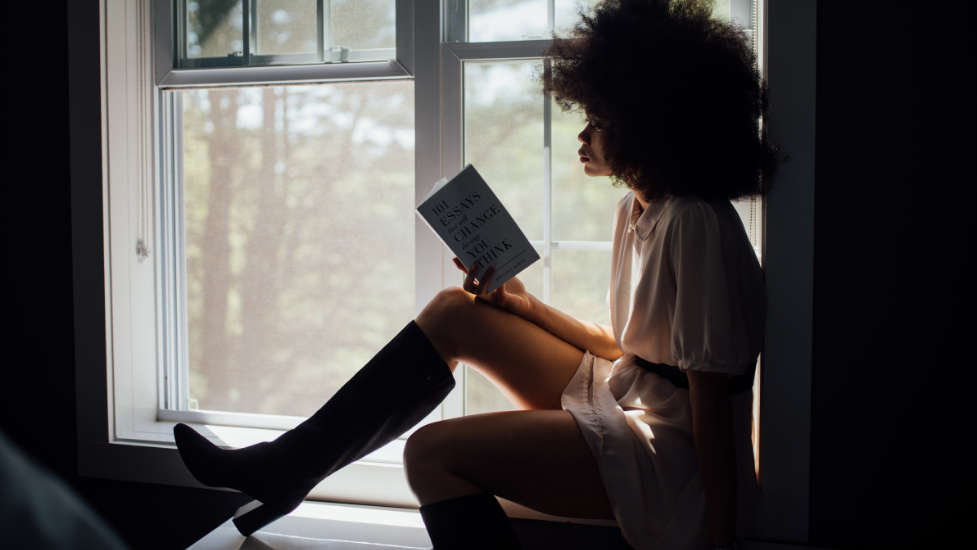 a woman standing in front of a window reading a book