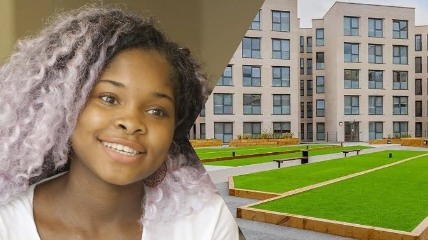 a young girl who is smiling at the camera and building behind