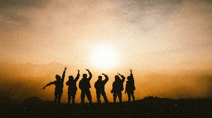 a group of people standing in front of a sunset
