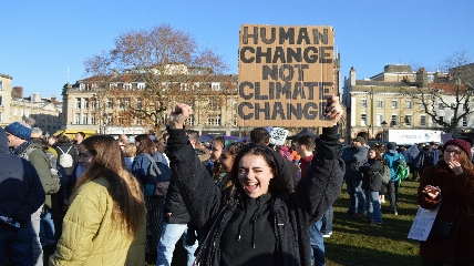 Activist standing in front of a crowd holding a sign