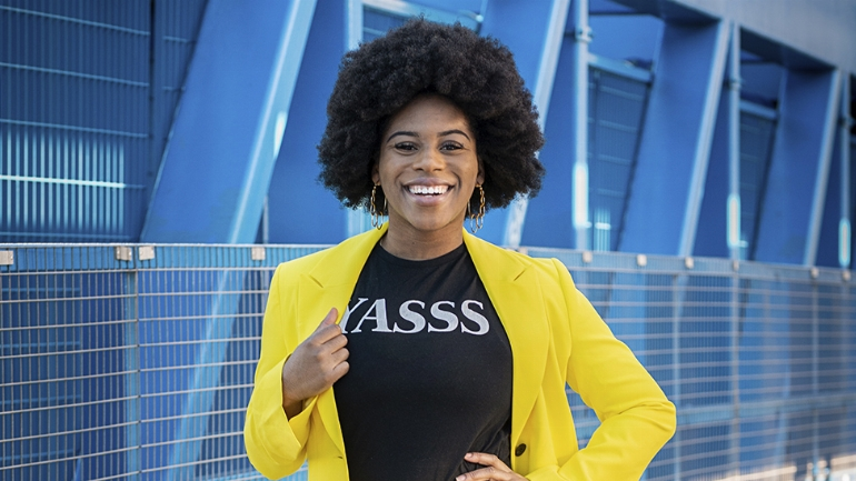 Bami stands tall with her dark afro, wearing a 'YASSS' t-shirt, and a bright yellow blazer
