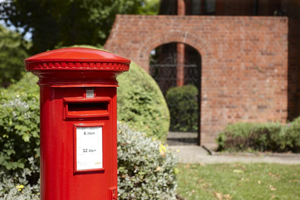 a post box in front of a brick building