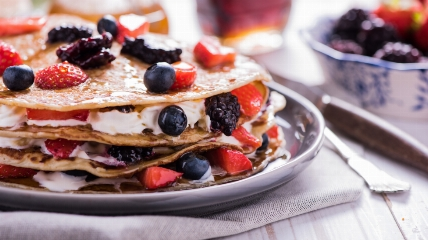 pancakes layered with with cream and fruit