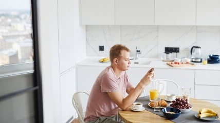 a person sitting at a kitchen table on their phone