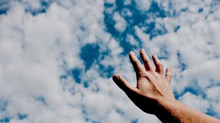 a hand holding a blue cloudy sky