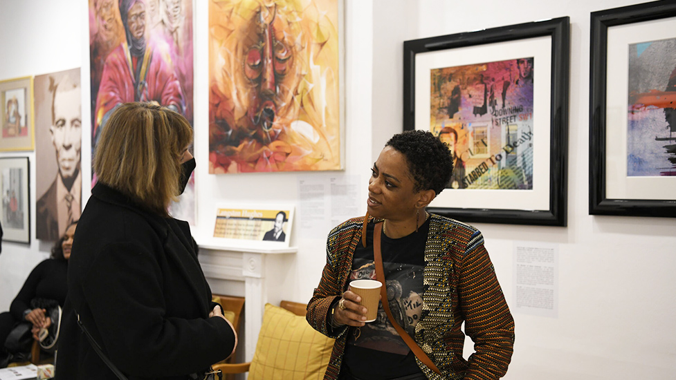 two women chatting, stood in front of a wall of art create by black artists
