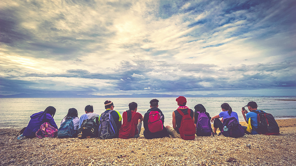 a group of people sitting at a beach