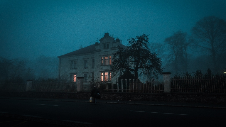 a house with trees in the dark