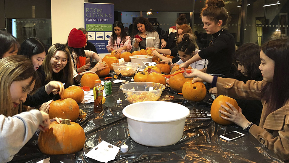 a group of people sitting at a table with pumpkins