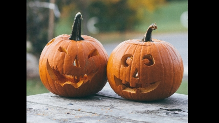 a close up of two carved pumpkins