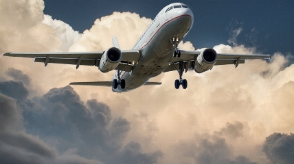 a large passenger jet flying through the air on a cloudy day