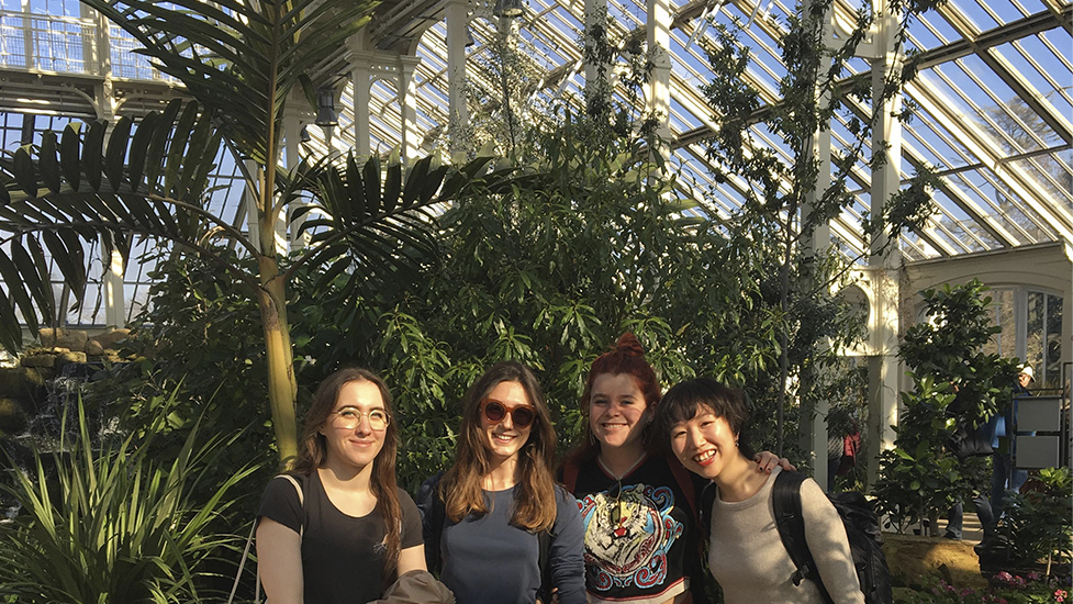 a couple of people standing in the glasshouse of Kew Gardens. It's sunny and the plants are bathing in the light.