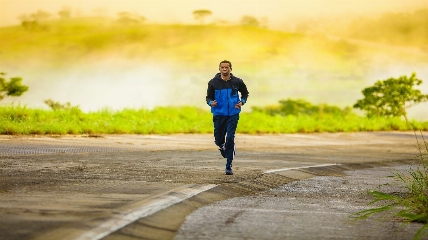 a man running down a road during sunrise
