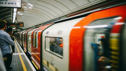 Tube in station and person standing on platform.