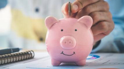 a person putting a coin into a piggy bank