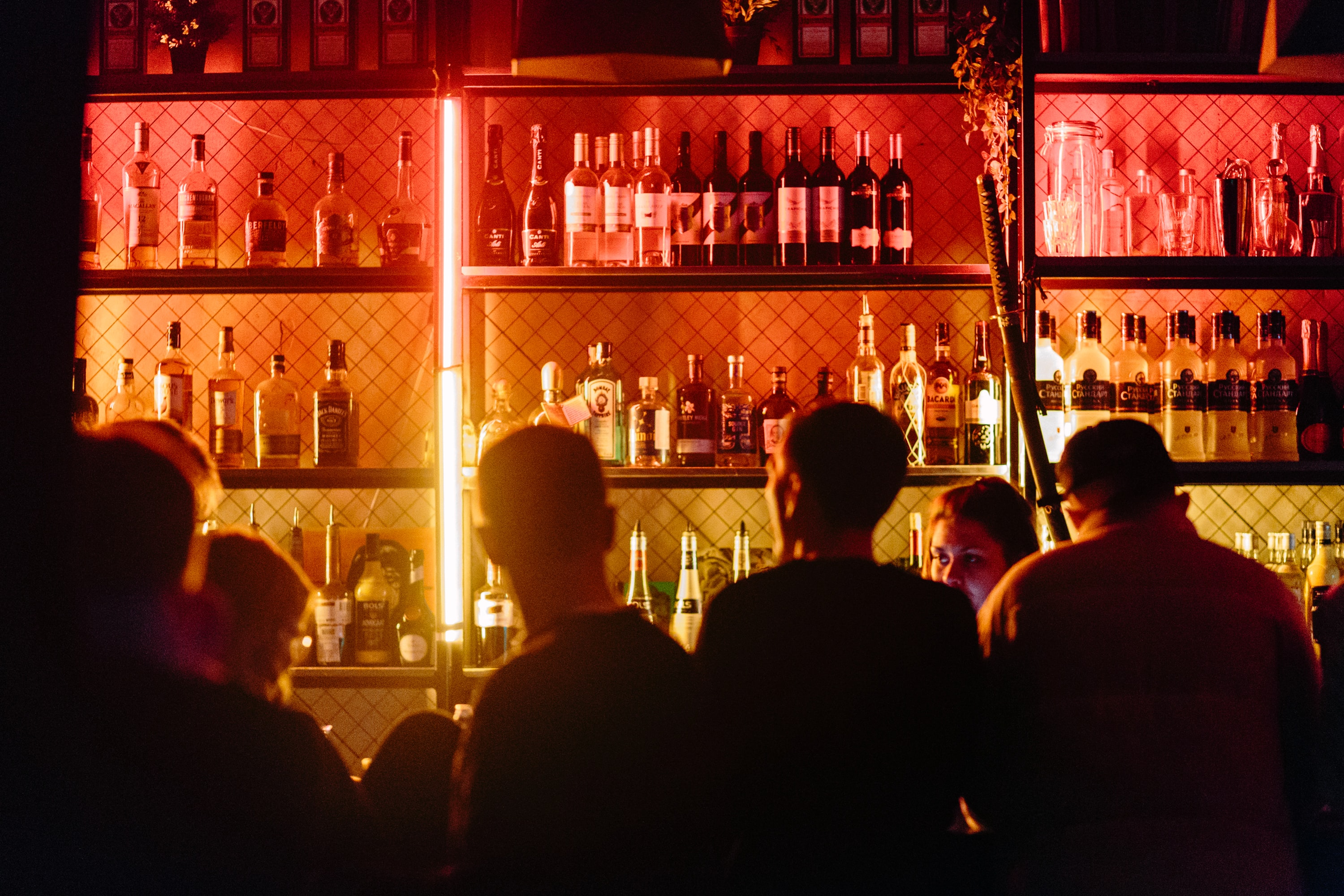 a group of people standing in front of a bar