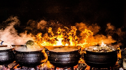 a large pot that is cooking on a grill