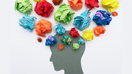colourful balls of paper coming out of the shape of someones head