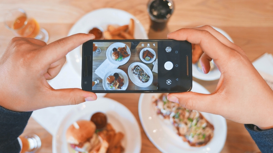a person taking a picture of food