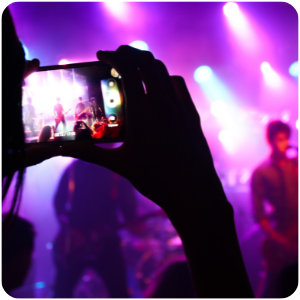 a person videoing a band on stage