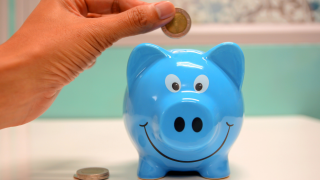 a close up of someone putting money in a piggy bank