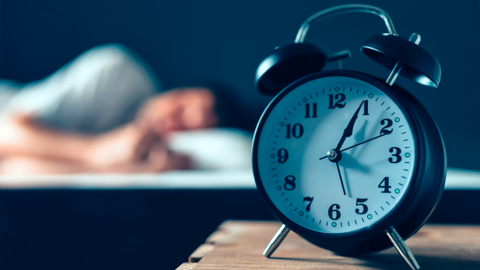 a close up of a clock on a table and a person asleep