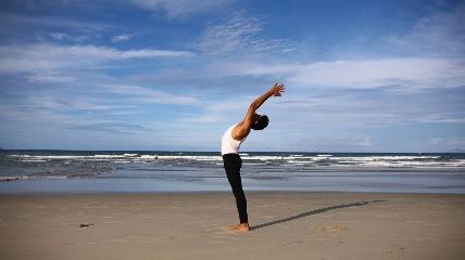 a man standing on a beach doing yoga