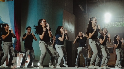 a group of people in a dance class in grey trousers and black tops