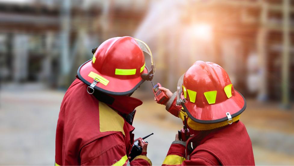 2 firemen wearing helmets