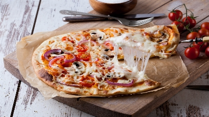 a slice of pizza sitting on top of a wooden table