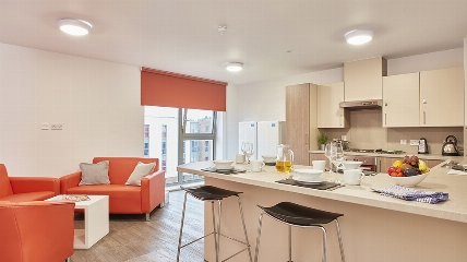 a kitchen with a large red chair in a room