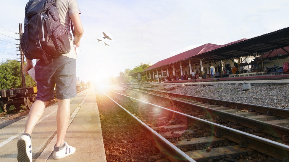 a person standing next to a train