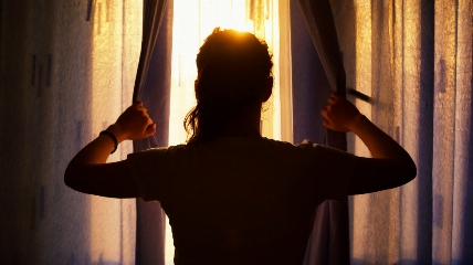 a person opening curtains