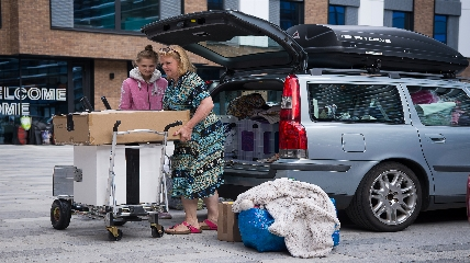 People unpacking from the car