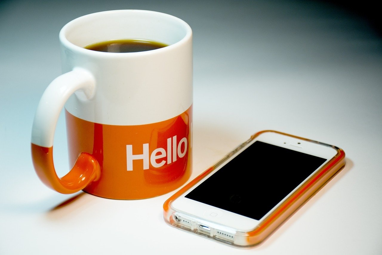 a cup of coffee on a table next to a smartphone