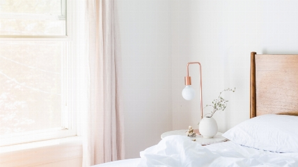 a bedroom with a bed and a lamp