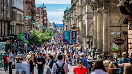 a crowd of people walking on a city street