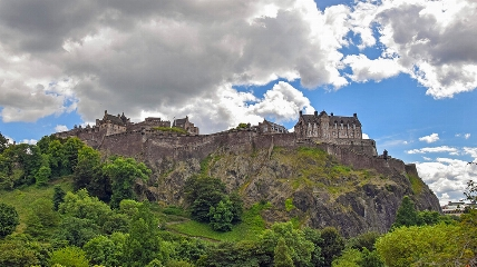 a large mountain in the background with Edinburgh Castle in the background