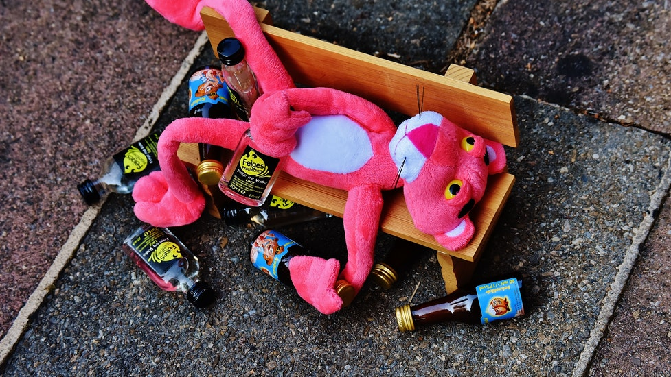 a close up of a toy lying on the floor surrounded by drink bottles