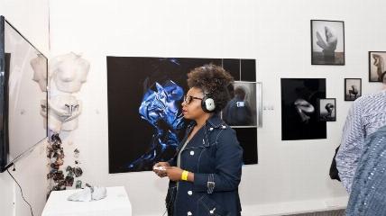 Girl looking at artwork with headphones